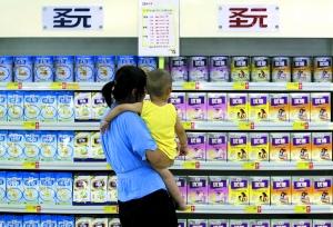 昨日,在山东潍坊一家超市,一名母亲抱着孩子站在贴有优惠活动广告的圣元奶粉专柜前。新华社发(孙树宝 摄)
