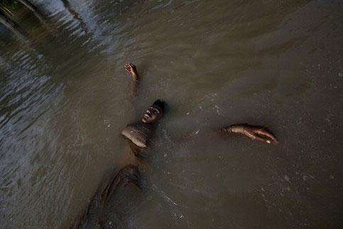 一名巴基斯坦男子的尸体浮在肮脏的水面上