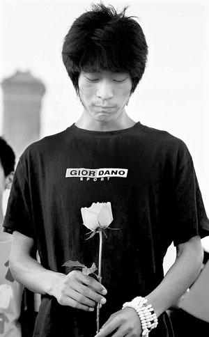 马浪旦拿着白色玫瑰在天安门广场为家乡祈福