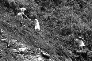 医护人员身背药品与氧气袋在山路上艰难前行