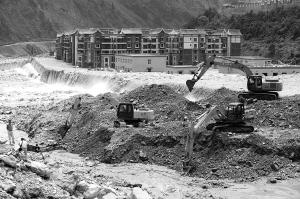经过连夜抢修,施工人员在被泥石流堵塞的岷江上挖出一条辅道