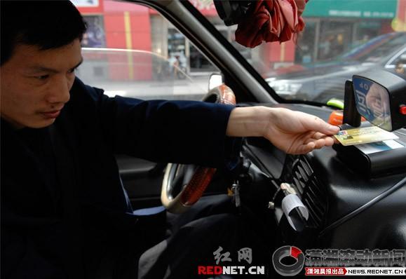 """资料图:长沙市民卡""""一触即可"""",以后市民就可以打车刷卡,一位市民体验打的刷卡,司机正在为他进行刷卡消费。潇湘晨报滚动新闻记者陈勇"""