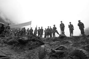 昨天下午,参与救灾的官兵伫立在泥泞中