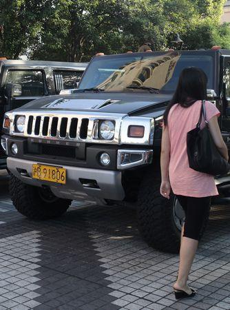 昨日,一名行人在一台悍马前走过。 早报见习记者 苗奥 图
