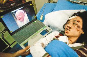 车祸发生后,小麟麟的母亲在在病床上看着孩子的照片,当时她尚不知小麟麟已经不在人世了。 (资料图片)