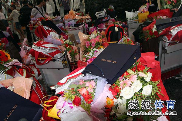 图文:中国羽毛球队载誉抵京 鲜花用车装