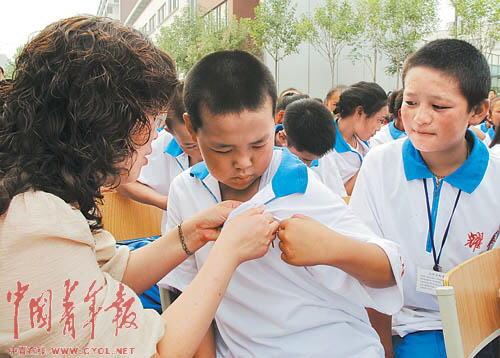 耀华滨海学校的教师为一名来自青海玉树的学生佩戴校徽。