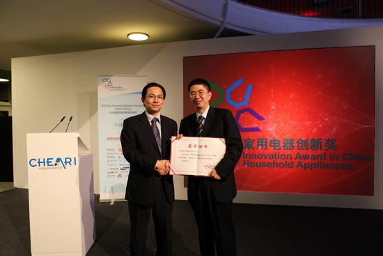 格力电器制冷技术研究院院长马颖江(右)从中国家用电器研究院院长邴旭卫手中接过证书