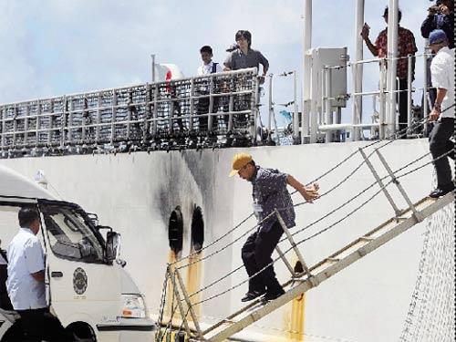 9月13日,在日本冲绳县石垣港,被日方扣押的我国渔船船员从日本海上保安厅巡逻船上走下,准备坐车前往石垣机场,乘国内来的包机返回祖国