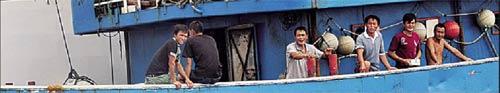 9月9日,被日本扣押的中国渔船停靠在日本石垣港,其上的中国船员在甲板上与新华社记者交流