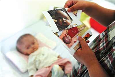 妈妈拿出朵朵出生后拍的一些照片。本报记者王海欣摄