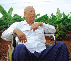 陈光保在自己的农场里,他身后就是一片香蕉林(中青报蒋昕捷供图)