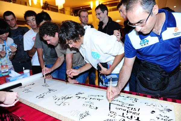 图文:2010年环中国赛圆满落幕 拿起毛笔签名