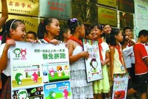 芦笛小学小学生在张宁的带领下在校门口宣传低碳出行理念