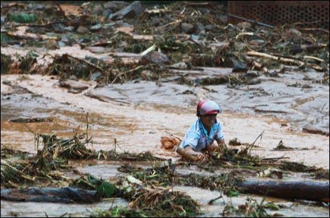 9月21日,广东高州市遭受洪涝灾害地区的一名居民向安全地带转移(来源:新华网