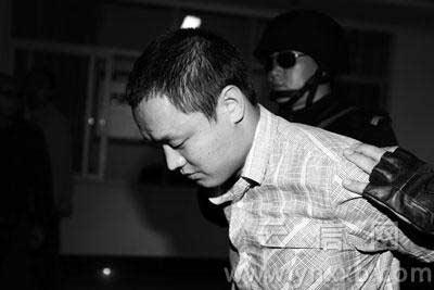 被押解回昆的赵永贵,表情很镇定. 记者夏德锐/摄图片