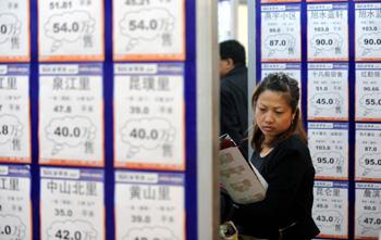 近日,在天津国际展览中心,一名市民在2010秋季天津房交会上的售楼信息板前驻足。新华社记者 李木子 摄