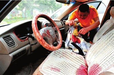 遇袭村主任的车内满是血迹,其朋友在整理血衣。 本报记者胡雪柏摄