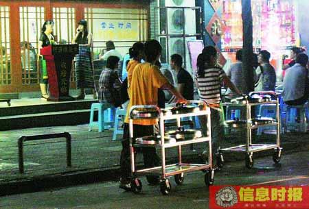 广和路某餐馆的服务员用手推车从餐馆外运送酸菜鱼到餐馆供给食客。