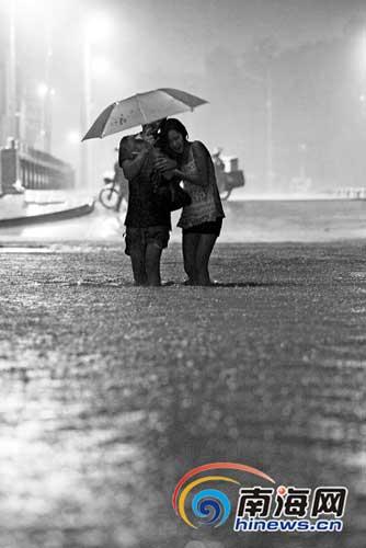 ▲17日凌晨5时52分,一对情侣艰难地在文昌市文城镇的积水中行走。本报记者刘孙谋摄
