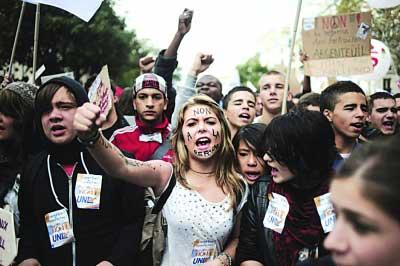 """一名法国女子在脸上写着""""不要改革""""。"""