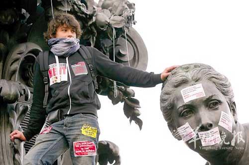 一年轻人站在雕塑上参加罢工,抗议法国政府关于养老制度的改革