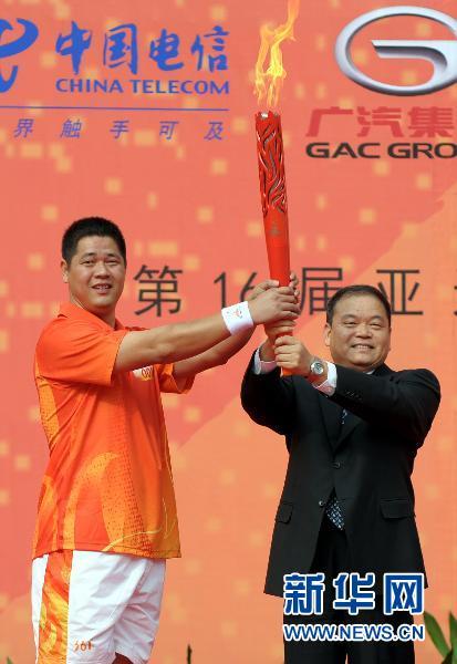 10月19日,惠州市委书记黄业斌(右)将亚运会火炬交给惠州站第一棒火炬手韩朝明。当日,第16届亚洲运动会火炬传递活动在惠州市举行,当天共有80名火炬手在9.4公里的路线上进行传递。新华社记者刘大伟摄
