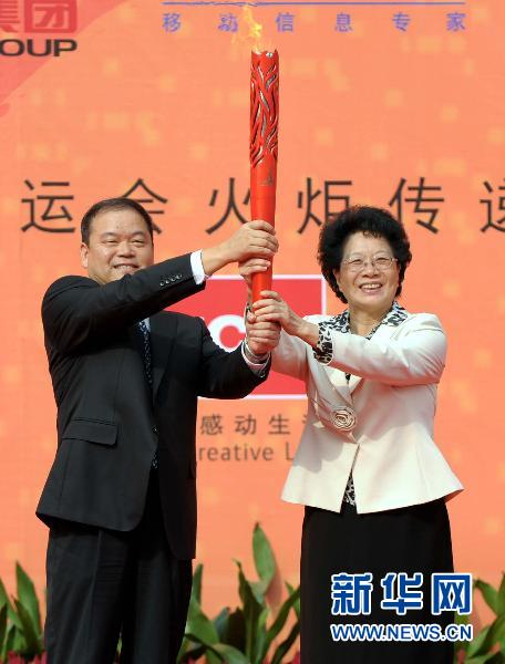 10月19日,第16届亚运会火炬传递中心主任杨武(右)将亚运会火炬交给惠州市委书记黄业斌。当日,第16届亚洲运动会火炬传递活动在惠州市举行,当天共有80名火炬手在9.4公里的路线上进行传递。新华社记者刘大伟摄