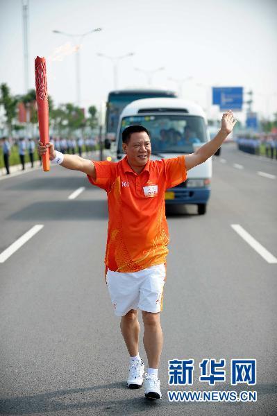 10月19日,亚运会火炬传递惠州站火炬手夏哲顺在传递中。当日,第16届亚洲运动会火炬传递活动在惠州市举行,当天共有80名火炬手在9.4公里的路线上进行传递。新华社记者刘大伟摄