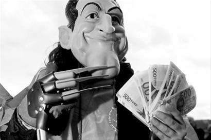 法国巴黎,一名抗议者戴着总统萨科齐的面具炫耀手中的钞票。IC图片