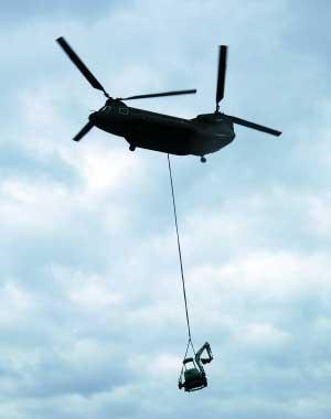 直升机吊挂挖土机前往苏花公路塌方处准备挖掘