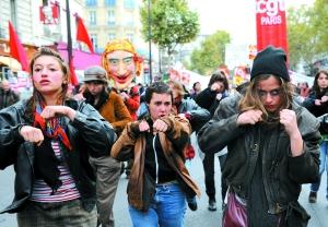 28日,法国巴黎,反对退休改革的游行进入到第九天,参加示威的年轻人作出击拳的姿势。