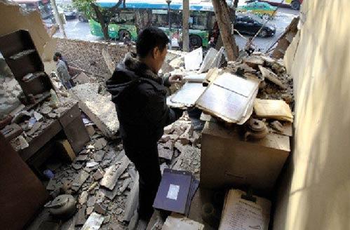 在一个被强拆的化工材料商店,老板刘先生在残垣断壁里找到了账本。本报记者 黄利健 摄