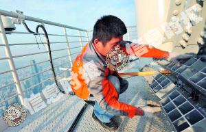 昨日下午,在广州塔天线桅杆500余米高处,于师傅仔细将焰火装置固定在塔尖平台上。信息时报记者 何建 摄
