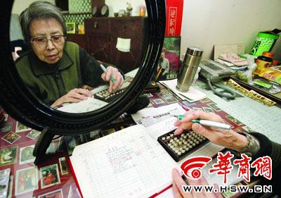 郭大妈将每日的花费计算后记录在账本上-本报记者张杰摄