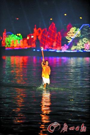 广东农民、龙舟运动发烧友吴国冲从海心沙岛旁近两百米的珠江江面上手持火炬踏波而来。新华社图