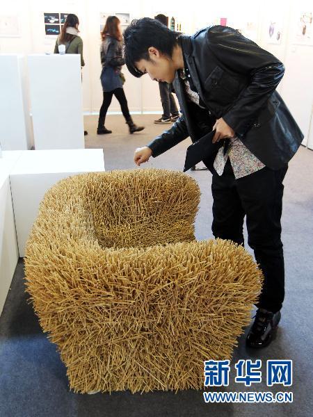 11月13日,在中国国际创意设计展上,一名观众参观用竹签制作的沙发.