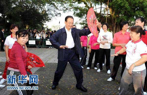 11月14日,国务院总理温家宝来到澳门大炮台花园,同在这里晨练的市民亲切交流,一起练习太极拳并学练太极扇。 新华社记者 饶爱民 摄