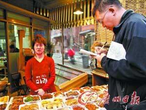 在首尔的一家市场,泡菜店老板正在接受本报记者采访。