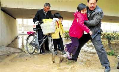 一位好心人把过马路的小学生一个个抱过去。 晚报记者 廖谦图