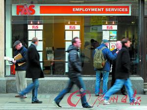 16日,在爱尔兰首都都柏林街头,一家职业介绍所的门外行人匆匆。