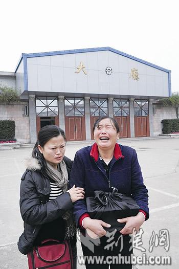 图为:姐姐魏肃英(右)抱着魏霞的骨灰盒悲痛地走出汉口殡仪馆 记者陈勇摄