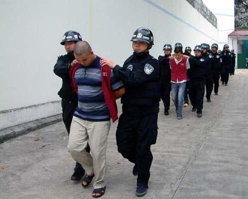 公安民警押解犯罪嫌疑人到犯罪现场进行辨认.