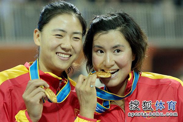 图文:女子沙滩排球颁奖仪式 开心轻咬金牌