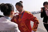 图文:帆板冠军王宁载誉回乡 整理绶带