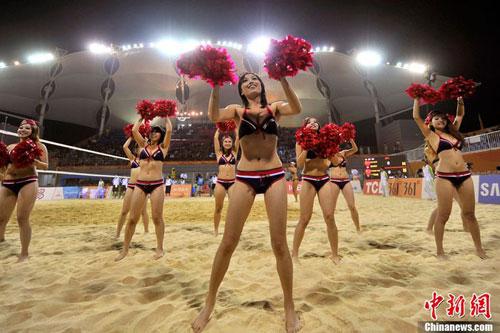 """11月23日晚,亚运女子沙排决赛赛场,激情四溢的沙排宝贝身着""""制服""""比基尼秀火爆辣舞令赛场气氛高潮迭起。中新网记者 金硕 摄"""