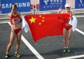 图文:女子马拉松周春秀夺冠 与队友一同庆祝