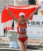 图文:女子马拉松周春秀夺冠 高举国旗开心庆祝