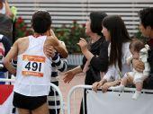 图文:男子马拉松池永骏夺冠 赛后激动亲吻妻子