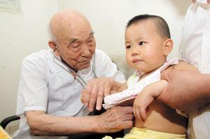 山崎宏老人在给孩子看病(摄于2009年) 记者 龚辉 摄